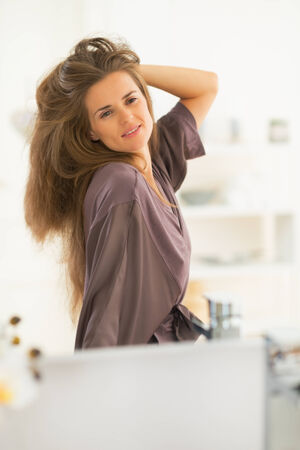 Portrait of young woman with long hair looking in mirror Stock Photo - 27700359