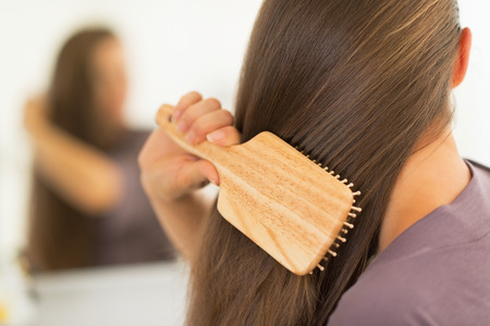 Closeup on young woman combing hair Stock Photo - 27700424