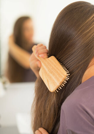 Closeup on young woman combing hair Stock Photo - 27700425