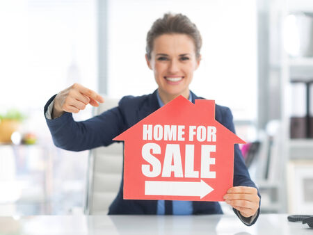 selling points: Happy woman pointing on home for sale sign
