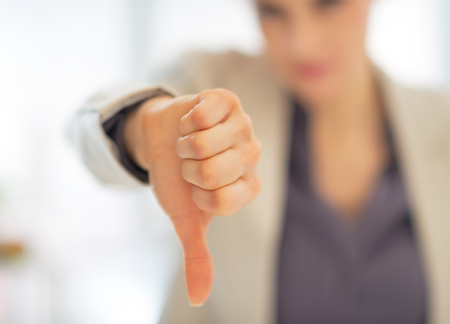 Closeup on business woman showing thumbs down photo