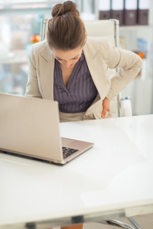 back strain: Closeup on business woman with back pain