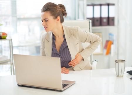 Business vrouw met buikpijn in het kantoor