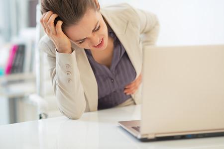 オフィスでビジネスの女性の胃と痛み