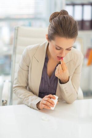 painkiller: Business woman taking pill at work