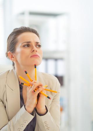 disarrangement: Portrait of thoughtful business woman holding pencils