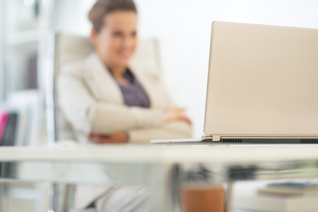 topicality: Closeup on laptop and business woman in background Stock Photo