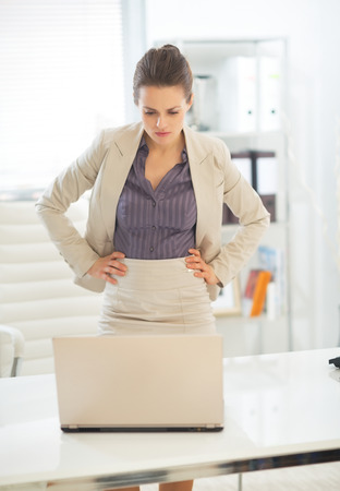 topicality: Thoughtful business woman looking on laptop in office Stock Photo