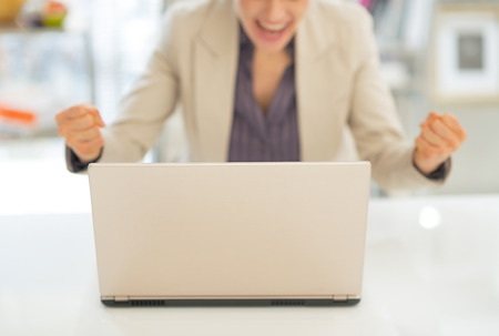 topicality: Closeup on laptop and happy business woman in background