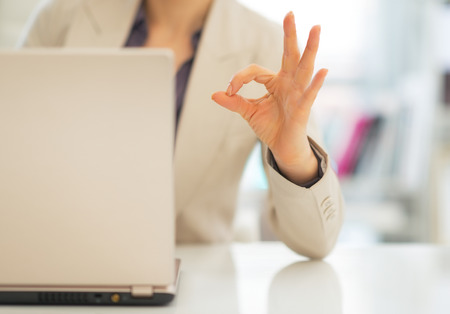 topicality: Closeup on business woman with laptop showing ok gesture