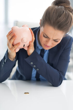 shaking out: Closeup on business woman shaking out coin from piggy bank Stock Photo