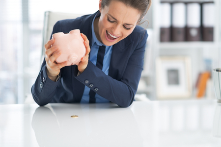 shaking out: Angry business woman shaking out coin from piggy bank Stock Photo