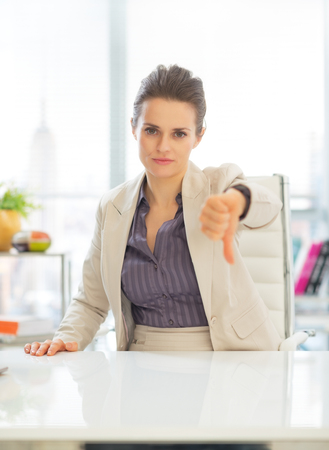 Business woman showing thumbs down photo