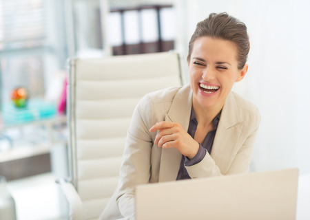 topicality: Laughing business woman with laptop Stock Photo