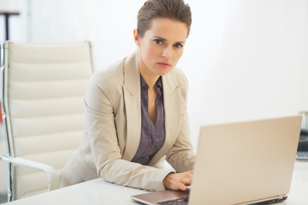 topicality: Thoughtful business woman working on laptop Stock Photo