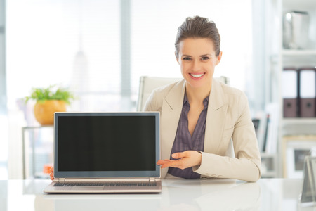 topicality: Happy business woman showing laptop blank screen