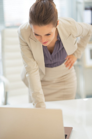 Thoughtful business woman looking on laptop in office Stock Photo