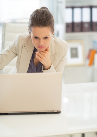 topicality: Thoughtful business woman working on laptop in office