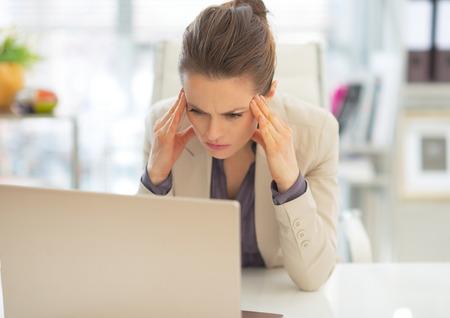 mujeres tristes: Subray� mujer de negocios con ordenador port�til en el trabajo Foto de archivo