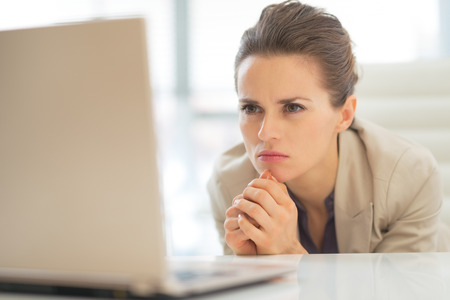 topicality: Thoughtful business woman with laptop at work