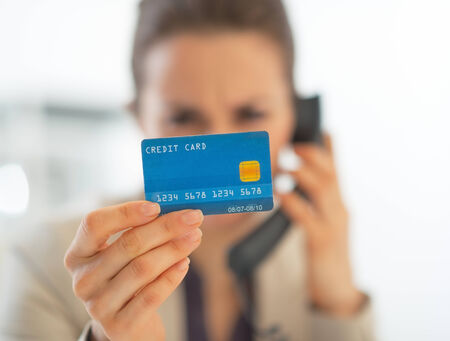anonym: Closeup on business woman with credit card talking phone in office