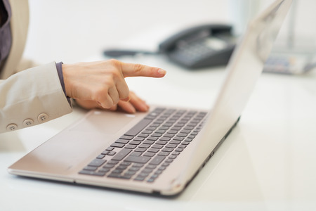 Closeup on business woman pointing in laptop Stock Photo - 28096271