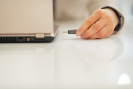 Closeup on business woman putting usb flash in laptop Stock Photo - 28096276