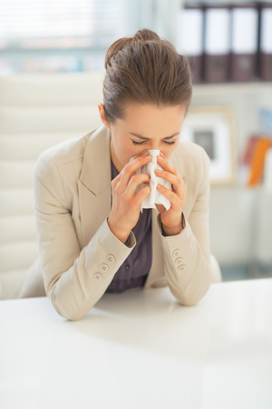Business woman in office blowing nose Stock Photo - 28131479