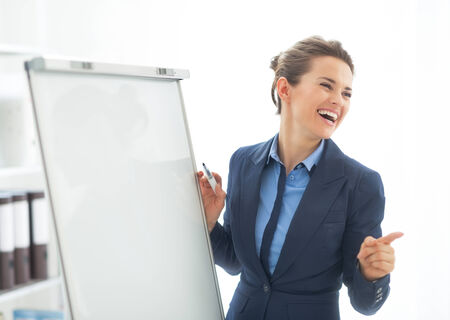Smiling business woman near flipchart pointing Stock Photo - 28131490