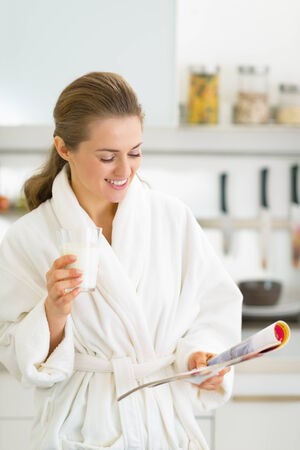 house robe: Happy young woman drinking milk in kitchen in the morning