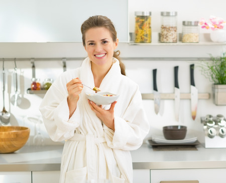 house robe: Portrait of smiling young woman eating muesli in kitchen in the morning