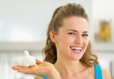 Portrait of happy young woman showing garlic