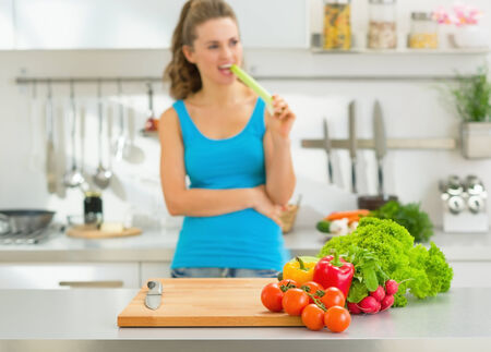 Closeup on fresh vegetables on table and young woman in background photo