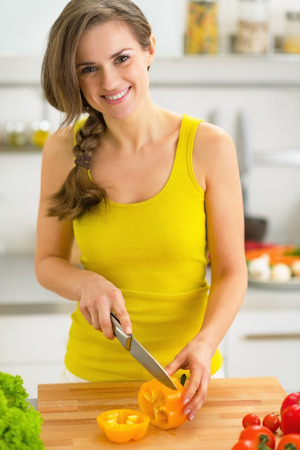 Happy young woman cutting bell pepper photo