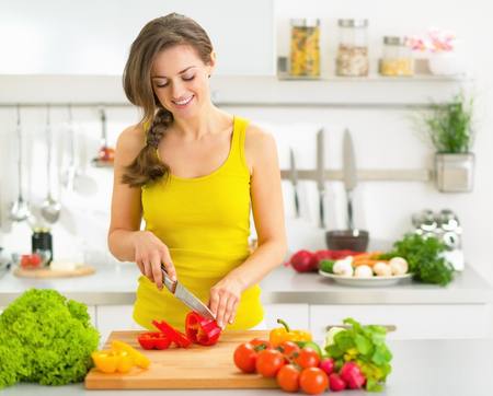 Happy young woman cutting fresh vegetables in kitchen photo