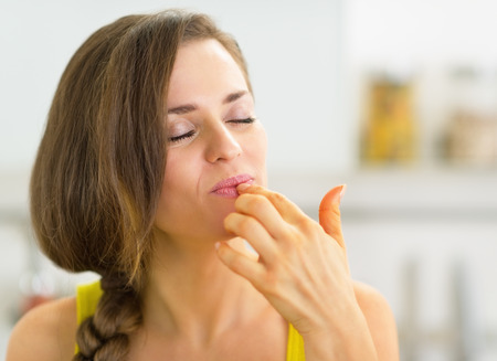 licking finger: Young woman in kitchen licking fingers Stock Photo