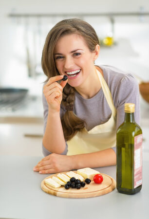 Portrait of happy young housewife eating cheese with olives photo