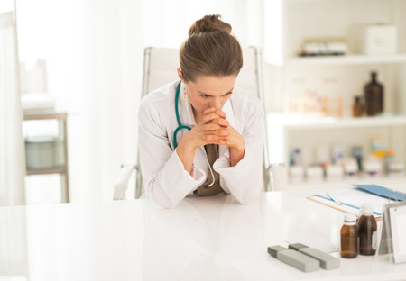 disquieted: Concerned medical doctor woman sitting in office