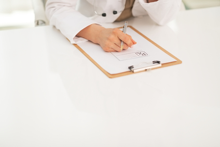 Closeup on medical doctor woman with clipboard photo