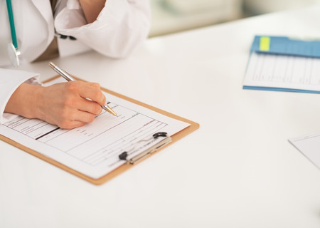 Closeup on medical doctor woman writing in clipboard photo