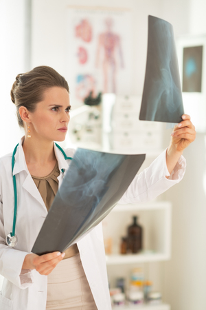 Medical doctor woman looking on fluorography in office Stock Photo - 28211139