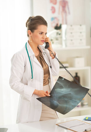 Medical doctor woman with fluorography talking phone in office Stock Photo - 28211140