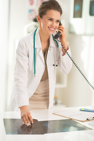 Happy medical doctor woman with fluorography talking phone in office Stock Photo - 28211142