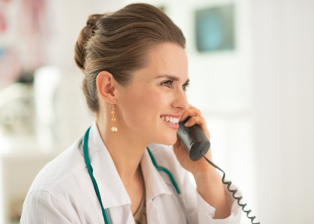 Portrait of smiling medical doctor woman talking phone Stock Photo - 28211144
