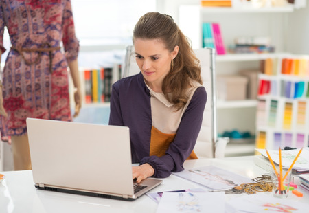 topicality: Fashion designer working on laptop in office Stock Photo