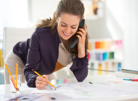 felicity: Smiling fashion designer in office talking phone