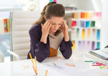 Portrait of stressed fashion designer in office
