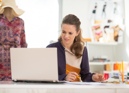 topicality: Fashion designer with laptop working in office Stock Photo