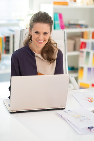 topicality: Smiling fashion designer working on laptop in office