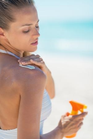 Young woman applying sun screen creme photo